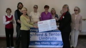 Val French accepting a cheque on behalf of A&T Umbrella from Tesco's community Representative